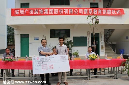 昆明分公司副总经理罗伟俊(左)向勐宽小学校长罗内(右)捐赠现金支票